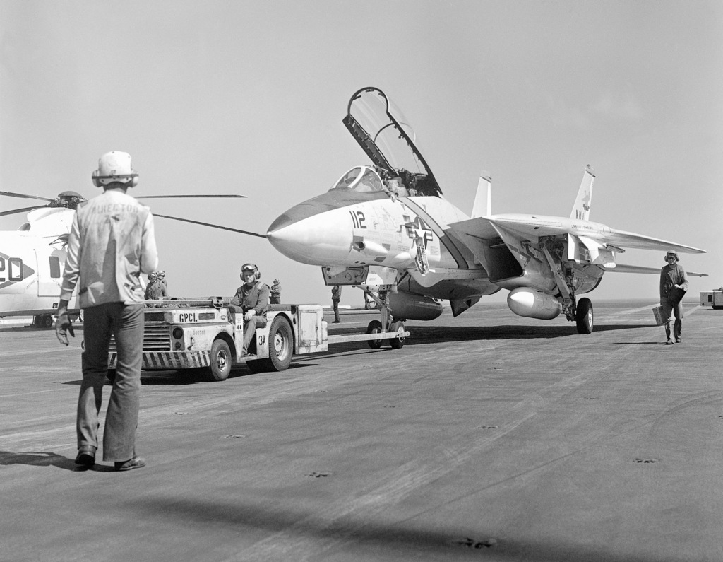 Flight deck crewmen move an F-14A Tomcat fighter aircraft with an MD-3 tow tractor aboard the aircraft carrier USS KITTY HAWK (CV 63)