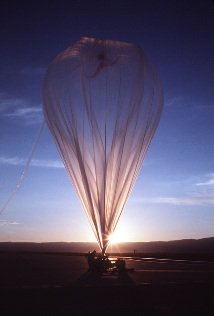 Members of the Balloon Research and Development Test Branch, Air Force Geophysics Laboratory, prepare to release a helium-filled balloon as dawn breaks