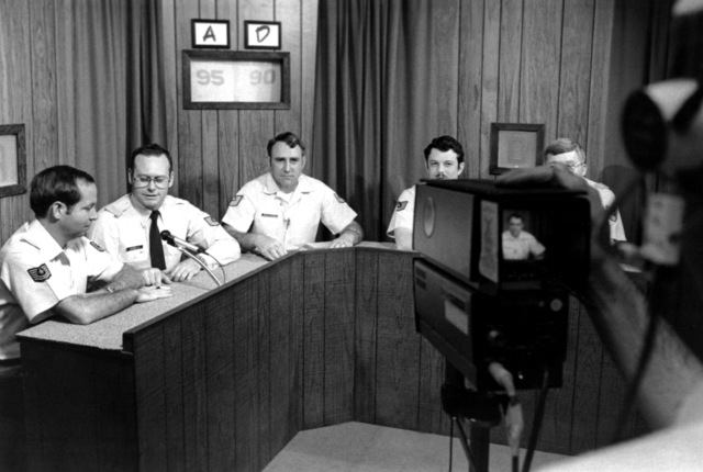 MSGT Vic Willoughby, Challenge 79 moderator, center, announces the team standings during a closed circuit television game show at the Strategic Air Command Non-Commissioned Officer Academy