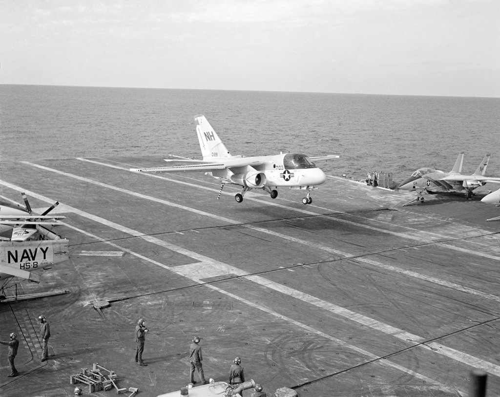 Right front view of an S-3A Viking antisubmarine aircraft preparing to make an arrested landing on the deck of the aircraft carrier USS KITTY HAWK (CV 63). F-14A Tomcat fighter aircraft are parked on the right