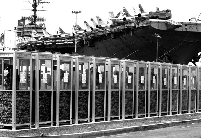 Sailors use some of the telephone booths on the pier beside the aircraft carrier USS CONSTELLATION (CV 64)