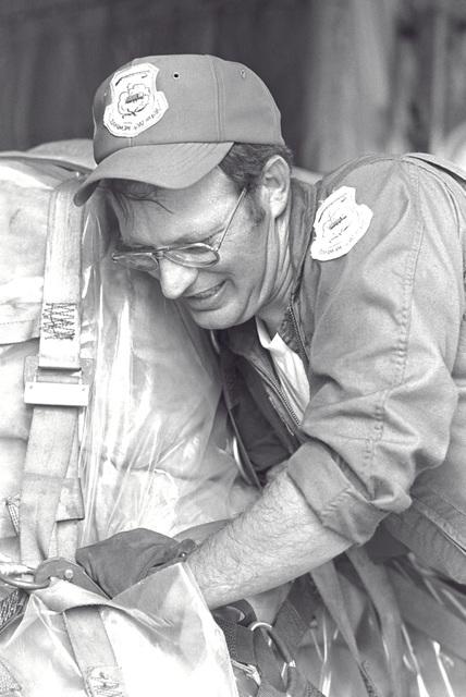 Technical Sergeant Robert G. Mynatt pushes a pallet of cargo into place aboard a C-130 Hercules aircraft