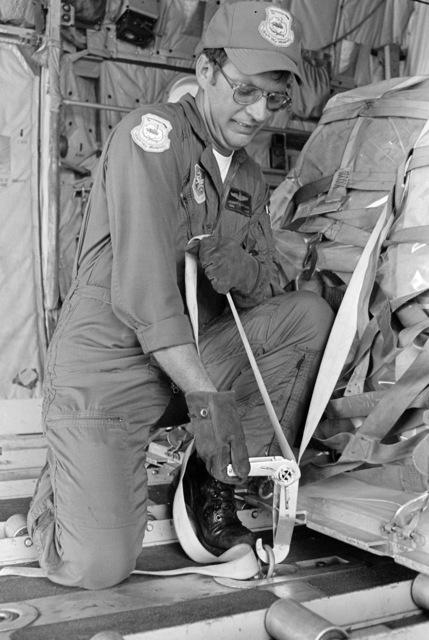 Technical Sergeant (TSGT) Robert G. Mynatt ratchets a tiedown strap around a pallet of cargo aboard a C-130 Hercules aircraft