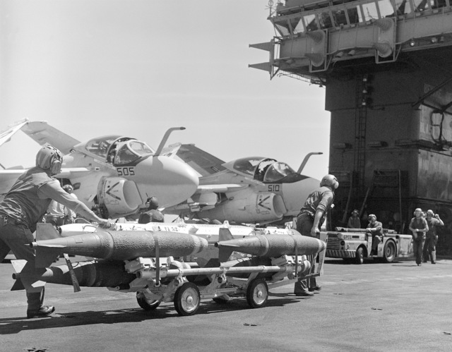 Two crewmen move Mk 82 500 pound bombs past two parked A6 Intruder attack aircraft during flight deck operations aboard the aircraft carrier USS KITTY HAWK (CV 63)