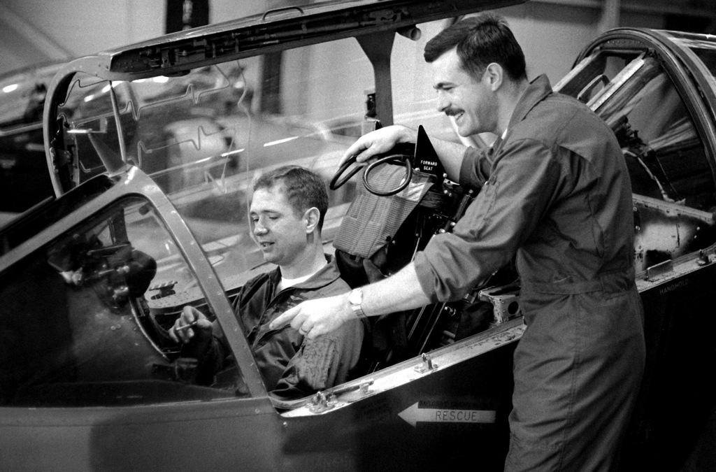 While 1LT Van Hunter sits in the cockpit of an AV-8A Harrier aircraft, CPT Terry Cuny explains some of the instruments to him. The men and equipment are a part of Marine Attack Squadron 203 (VMA-203)