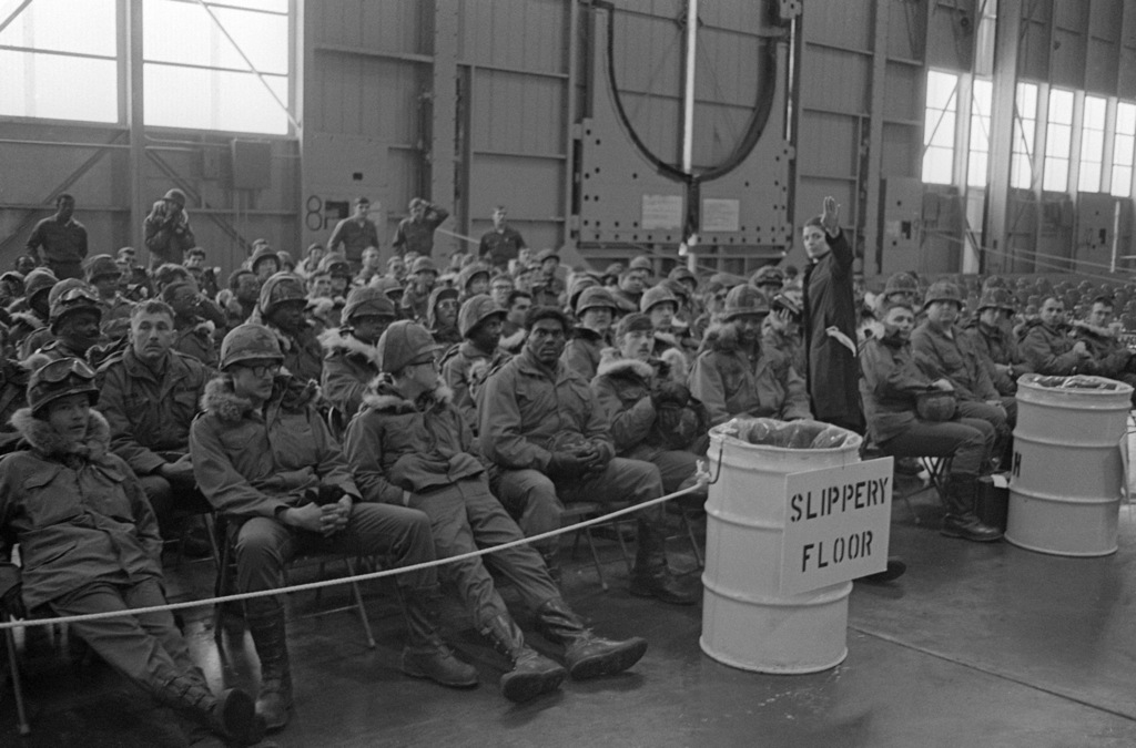 A member of the military Airlift Command briefs US Army troops on the location of various base facilities available to them.  The soldiers are stopping over at the base while en route to West Germany for Exercise REFORGER 79