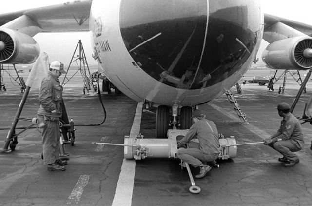 Maintenance personnel service a Military Airlift Command C-141 Starlifter aircraft on the flight line.  The aircraft is stopping over at the base while transporting US Army troops to West Germany for Exercise REFORGER 79