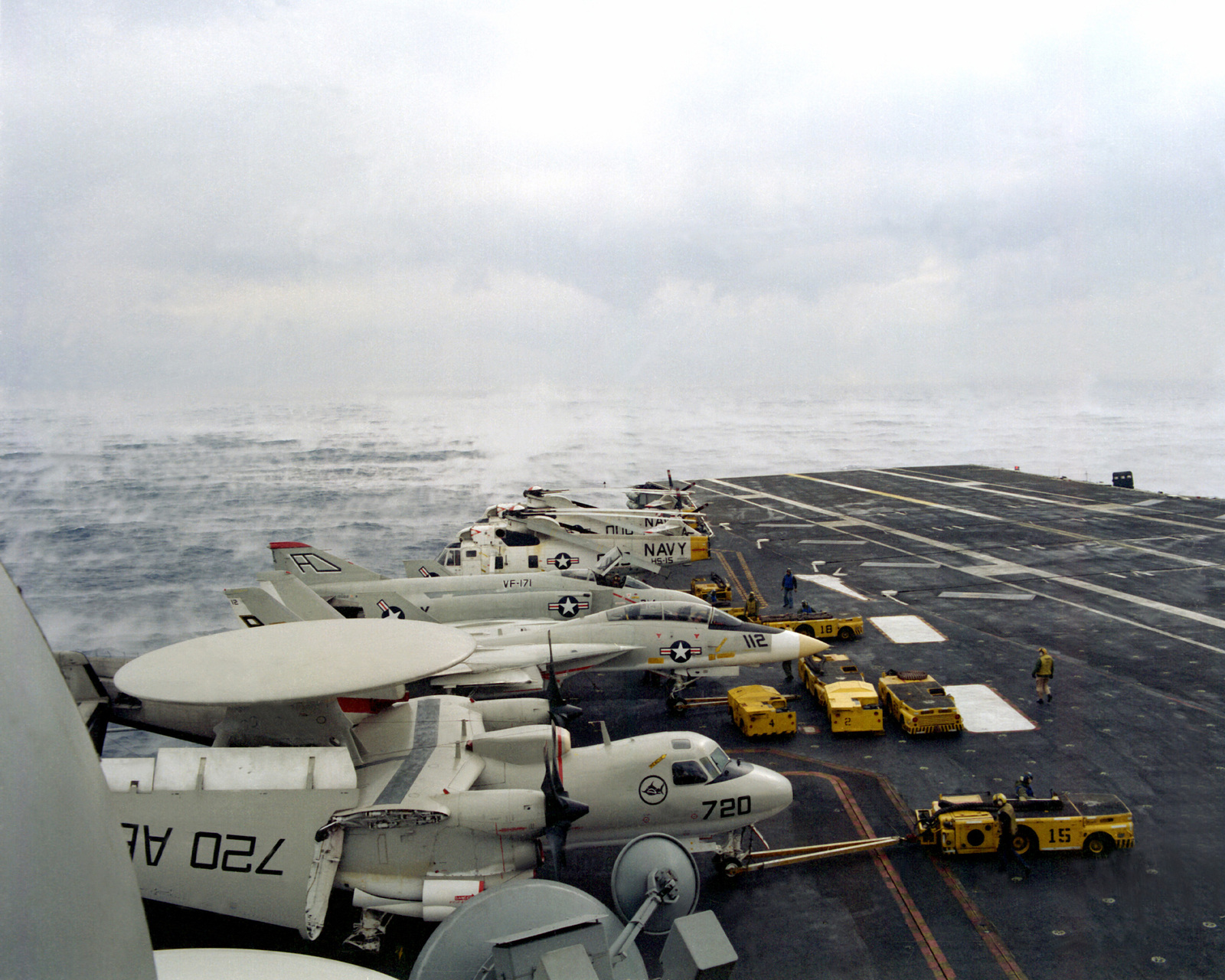 A view of an E-2 Hawkeye aircraft, and F-14 Tomcat aircraft, an F-4 Phantom II aircraft, and several SH-3 King helicopters on the flight deck of the USS INDEPENDENCE (CV-62) as the aircraft carrier encounters a dense sea mist