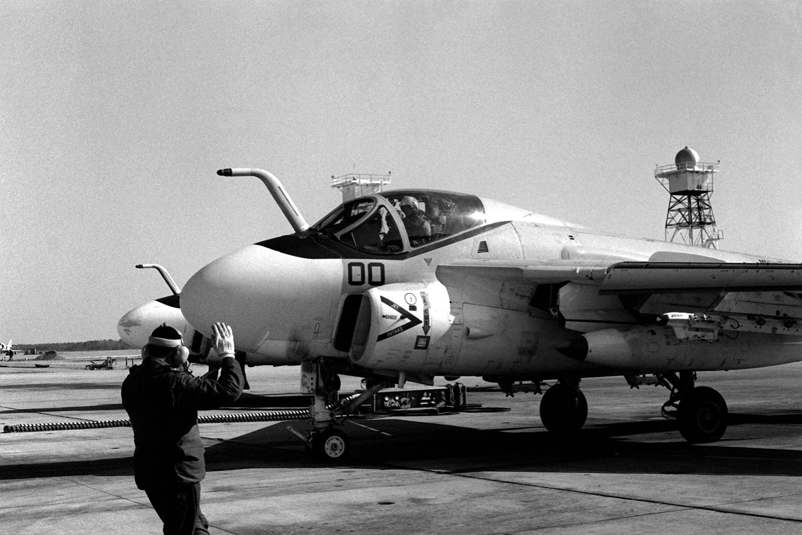 A flight line plane captain directs the pilot of an A-6E Intruder aircraft to a parking spot on the flight line of Marine All-Weather Medium Attack Squadron 533
