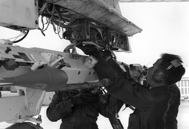 Two Marines from the ordnance section place a practice bomb under the wing of an A-6E Intruder aircraft
