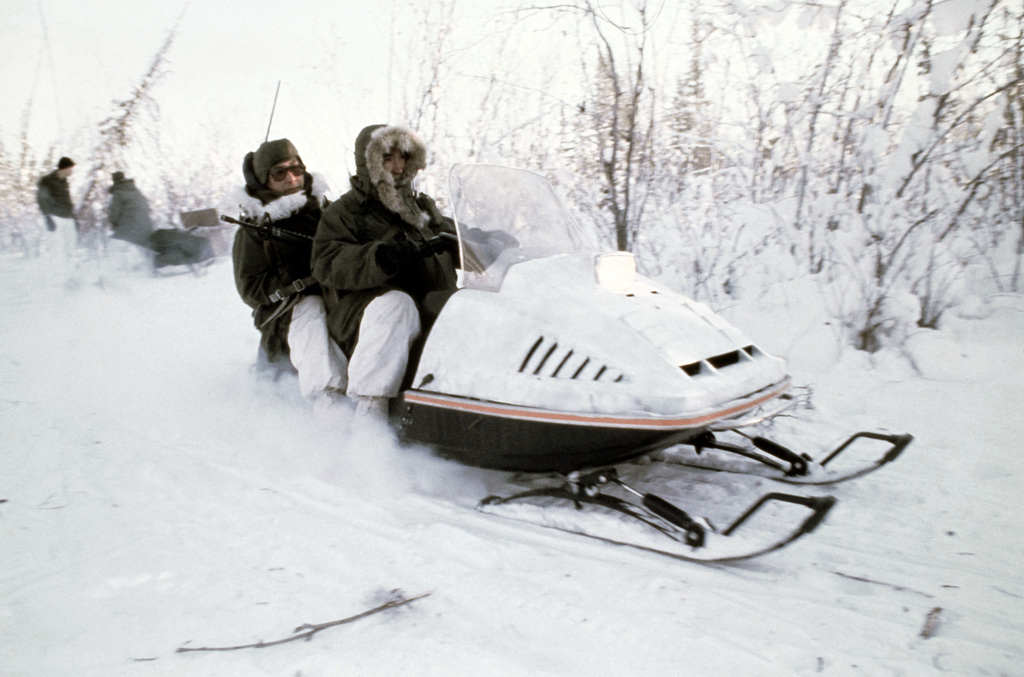 Members of Company A, 2nd Battalion, Army Special Forces, and Company B, 297th Infantry, Eskimo Scouts, move out on a reconnaissance mission using snowmobiles during Exercise JACK FROST '79