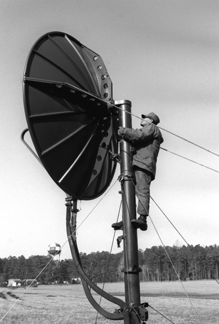 LCPL Muluaney makes an adjustment to a multi-channel radio antenna