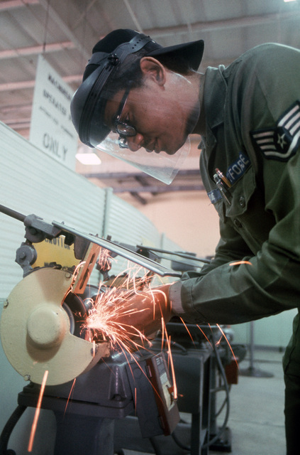 Staff Sergeant (SSGT) Rupert Davis of the 317th Field Maintenance Squadron puts the finishing touches on a specially fabricated tool in the machine shop
