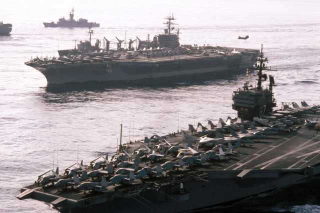 A port bow view of ships in Carrier Battle Group Eight underway off the coast of Lebanon. They are: front to back: the aircraft carrier USS JOHN F. KENNEDY (CV 67), nuclear-powered aircraft carrier USS NIMITZ (CVN 68), replenishment oiler USS KALAMAZOO (AOR 6), and the frigate USS W.S. SIMS (FF 1059)