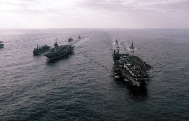 A port bow view of ships in Carrier Battle Group Eight underway off the coast of Lebanon. They are: left to right: the replenishment oiler USS KALAMAZOO (AOR 6), replenishing the nuclear-powered aircraft carrier USS NIMITZ (CVN 68), an unidentified auxiliary ship, guided missile cruiser USS JOSEPHUS DANIELS (CG 27), frigate USS W.S. SIMS (FF 1059), guided missile destroyer USS RICHARD E. BYRD (DDG 23), and the aircraft carrier USS JOHN F. KENNEDY (CV 67)