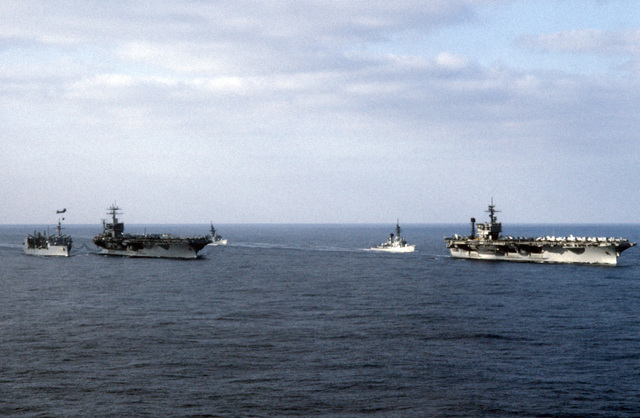 A starboard bow view of ships in Carrier Battle Group Eight underway off the coast of Lebanon. They are: left to right: the replenishment oiler USS KALAMAZOO (AOR 6), replenishing the nuclear-powered aircraft carrier USS NIMITZ (CVN 68), frigate USS W.S. SIMS (FF 1059), the guided missile destroyer USS RICHARD E. BYRD (DDG 23), and the aircraft carrier USS JOHN F. KENNEDY (CV 67)