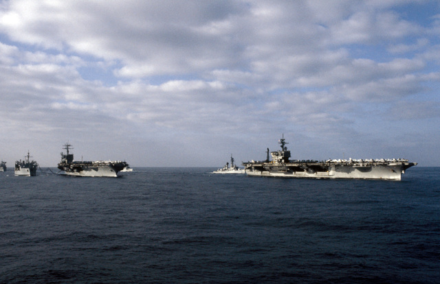 A starboard bow view of ships in Carrier Battle Group Eight underway off the coast of Lebanon. They are: left to right: the replenishment oiler USS KALAMAZOO (AOR 6), replenishing the nuclear-powered aircraft carrier USS NIMITZ (CVN 68), guided missile destroyer USS RICHARD E. BYRD (DDG 23), and the aircraft carrier USS JOHN F. KENNEDY (CV 67)