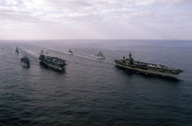 A starboard bow view of ships in Carrier Battle Group Eight underway off the coast of Lebanon. They are: left to right: the guided missile cruiser USS JOSEPHUS DANIELS (CG 27), replenishment oiler USS KALAMAZOO (AOR 6), replenishing the nuclear-powered aircraft carrier USS NIMITZ (CVN 68), frigate USS W.S. SIMS (FF 1059), guided missile destroyer USS RICHARD E. BYRD (DDG 23), and the aircraft carrier USS JOHN F. KENNEDY (CV 67)