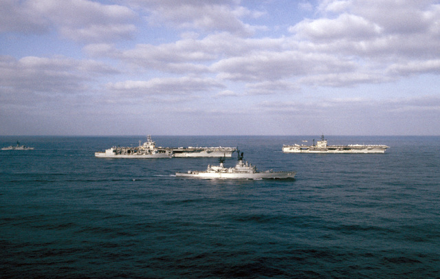 A starboard view of US Navy ships of Carrier Battle Group Eight off the coast of Lebanon. The ships are, left to right: the frigate USS W.S. SIMS (FF 1059), replenishment oiler USS KALAMAZOO (AOR 6), nuclear-powered aircraft carrier USS NIMITZ (CVN 68), guided missile cruiser JOSEPHUS DANIELS (CG 27) and the aircraft carrier USS JOHN F. KENNEDY (CV 67)