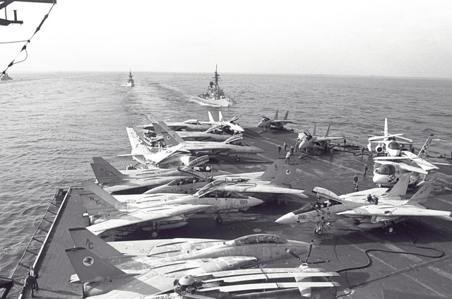 F-14A Tomcat and other aircraft parked on the flight deck of the aircraft carrier USS JOHN F. KENNEDY (CV-67). The frigate USS W. S. SIMS (FF-1059) and the guided missile destroyer USS RICHARD E. BYRD (DDG-23) are in the background