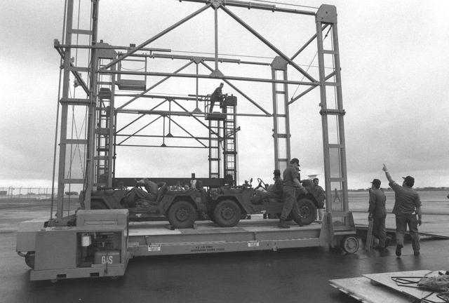 Air Force personnel position US Army M151 light vehicles on a Cochran loader for loading aboard a cargo aircraft. The vehicles are being shipped to Korea for use in exercise TEAM SPIRIT '79