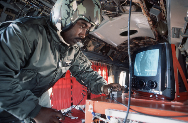 A 20th Special Operations Squadron flight mechanic inspects a videotape player and monitor aboard a UH-1N Iroquois helicopter during Exercise J-CATCH, a joint rotary wing and fixed wing tactics development and capability evaluation