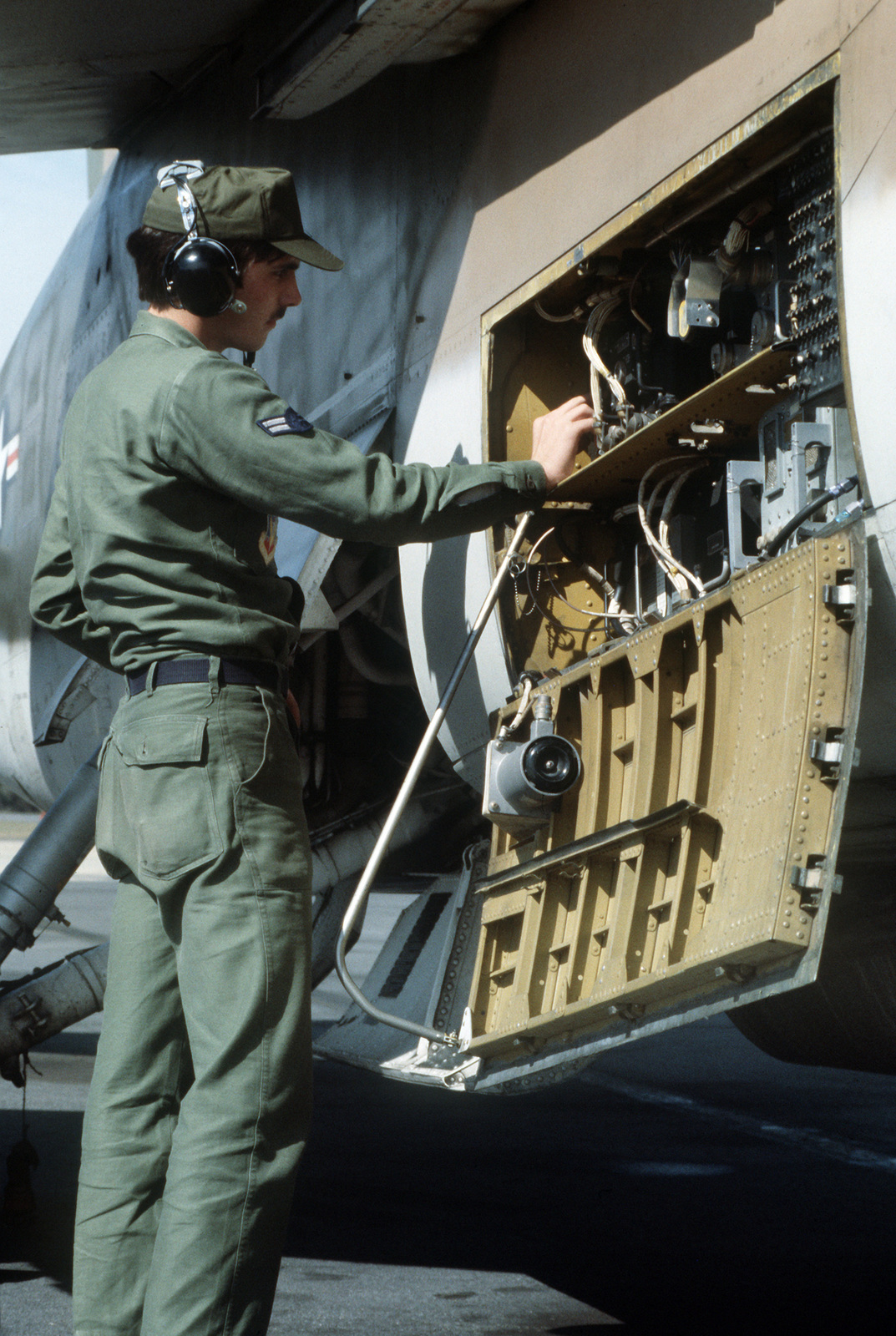 A member of the 355th Aircraft Generation Squadron inspects avionics equipment on a A-7 Corsair II aircraft participating in exercise J-Catch, a joint rotary wing and fixed wing tactics development and capability evaluation