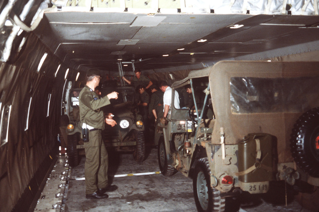 Members of the 619th Military Airlift Support Squadron secure US Army M151 vehicles aboard a Flying Tigers 747 contract aircraft. The vehicles are being shipped to Korea for use during exercise TEAM SPIRIT '79