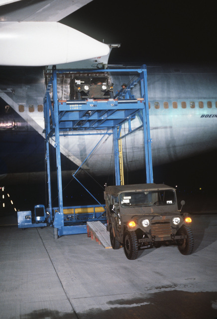 Members of the 619th Military Airlift Support Squadron use a Cochran loader to load US Army M151 vehicles aboard a Flying Tigers 747 contract aircraft. The vehicles are being shipped to Korea for use during exercise TEAM SPIRIT '79