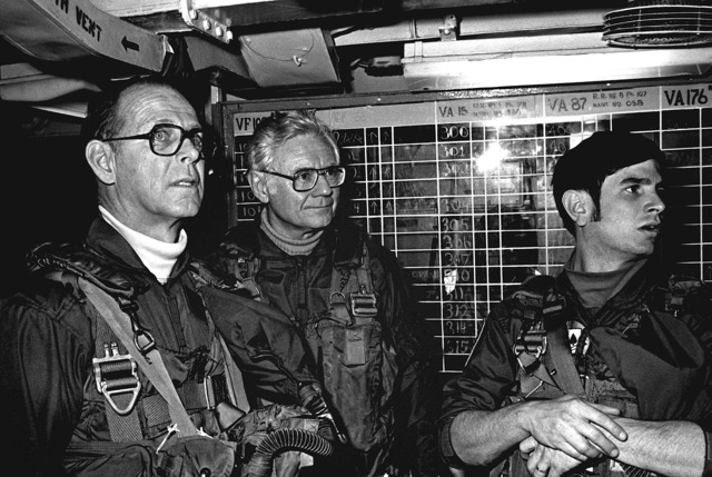 Undersecretary of the Navy Robert Baldwin, left, a member of his party, center, and a pilot from the Air Anti-submarine Squadron 28 (VS-28) in flight gear during Baldwin's visit aboard the aircraft carrier USS INDEPENDENCE (CV-62)