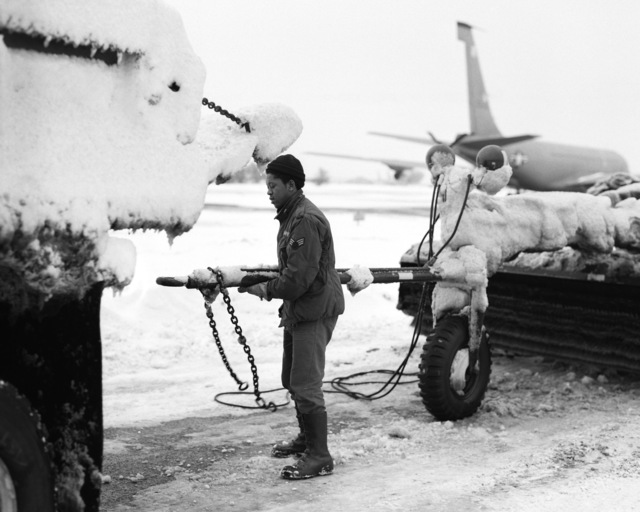 SENIOR AIRMAN (SRA) Jesse F. Parks of the 513th Civil Engineering Squadron drafting section prepares to hook up a snow broom to help keep the flight line clear of snow