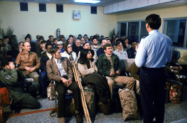 Evacuees from the US Embassy in Tehran, Iran, are briefed upon their arrival at the air base terminal