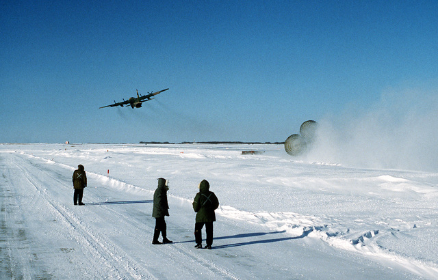 A U.S. Air Force C-130 Hercules aircraft makes a low-altitude parachute extraction system (LAPES) drop on a snow-covered runway during a test at Namo, Canadian Air Force Base