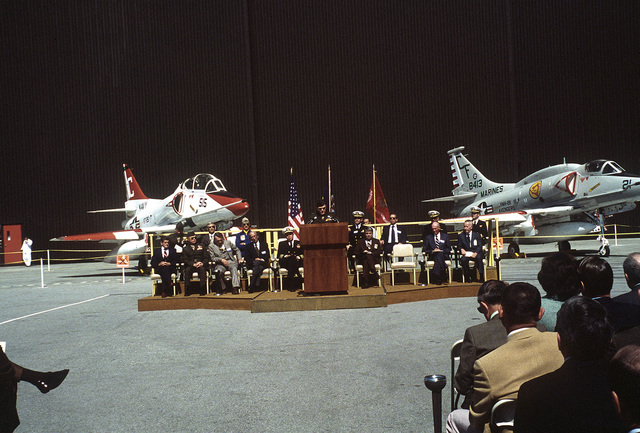 A wide view of the exhibit and ceremony for the last A-4 Skyhawk aircraft built by McDonnell Douglas Corporation. A Marine major general at the podium speaks to the honored guests and spectators