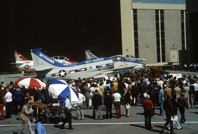During the exhibit and ceremony for the last A-4 Skyhawk aircraft built by McDonnell Douglas Corporation, many of the spectators gather around an A-4M Skyhawk that is beautifully painted. Two other A-4 aircraft are in the background