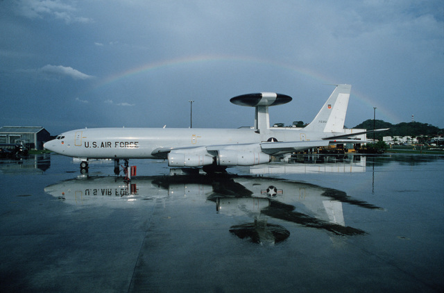 A left side view of a parked E-3A airborne warning and control system aircraft during exercise Black Fury II. The aircraft is reflected in the rain water on the ramp and a rainbow is visible in the background. Bi-monthly Aerospace Audio Visual Service PHOTO Contest, Color Entry, Jul. 1980