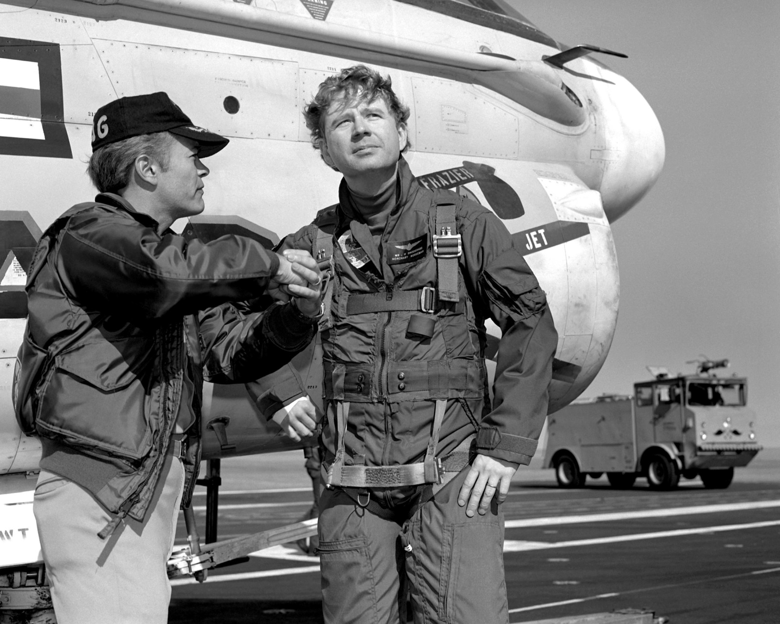 A Navy pilot talks to Charles Snodgrass, right, a distinguished visitor, as they stand on the flight deck of the aircraft carrier USS INDEPENDENCE (CV-62)