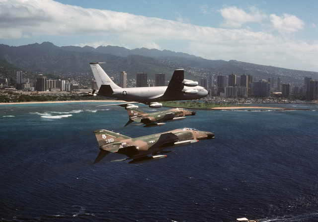 An air to air right side view of two 199th Tactical Fighter Squadron F-4 Phantom II aircraft flying in formation with a 161st Air Refueling Group KC-135 Stratotanker aircraft. In the background is the Honolulu skyline