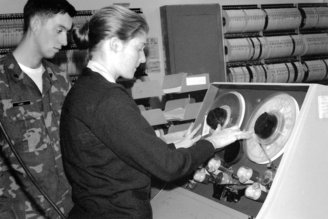 Woman Marine LCPL Sherry Bateman instructs CPL Donald Lane on how to operate the tape cleaner for computer tapes