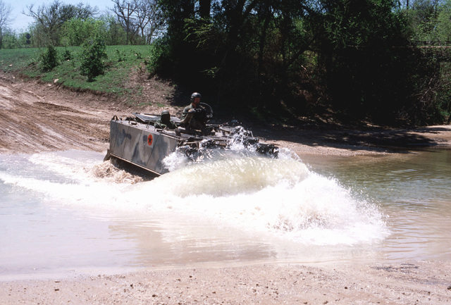 A 2nd Armored Division M-113 armored personnel carrier fords a rian-swollen stream during joint Air Force and US Readiness Command training exercise Brave Shield XIX