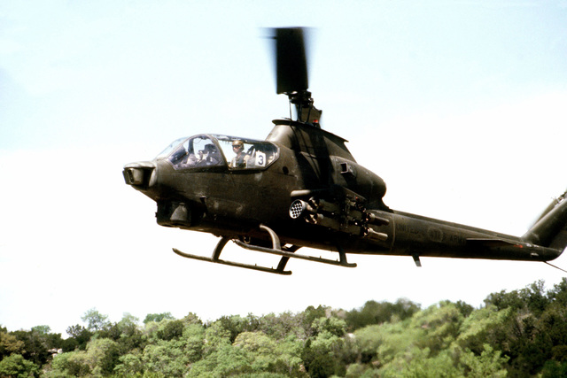 A left side view of an AH-1 Cobra helicopter in low-level flight during the joint Air Force and US Readiness Command training exercise Brave Shield XIX