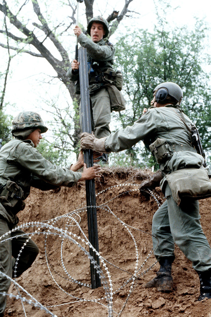 Members of Company A, 8th Engineers lay concertina wire at a river crossing during joint Air Force and US Readiness Command training exercise Brave Shield XIX