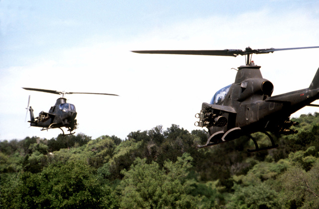 Two AH-1 Cobra helicopters face each other while hovering at low altitude during joint Air Force and US Readiness Command training exercise Brave Shield XIX