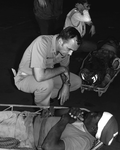 CDR John Calhoun, executive officer of the aircraft carrier USS INDEPENDENCE (CV-62), talks with one of two civilians just rescued at sea by Helicopter Squadron 15 (HS-15)