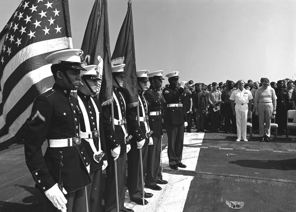 A U.S. Marine Corps color guard stands at attention during a memorial service on the flight deck of the aircraft carrier USS INDEPENDENCE (CV-62)
