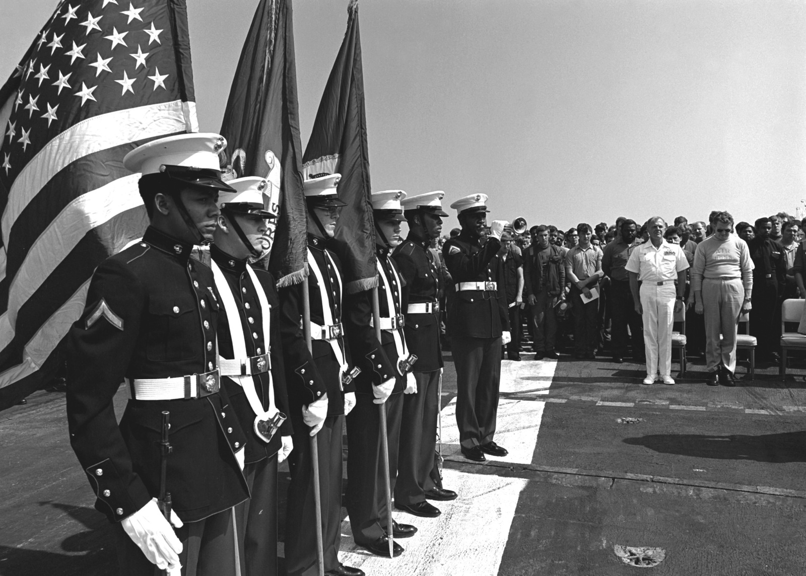 a u s  marine corps color guard stands at attention during a memorial service on the flight deck