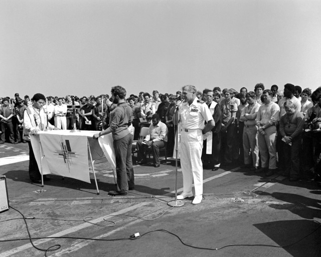 CAPT Thomas C. Watson Jr., commanding officer, delivers the eulogy at a memorial service on the flight deck of the aircraft carrier USS INDEPENDENCE (CV-62). The service is being held for an INDEPENDENCE crewman