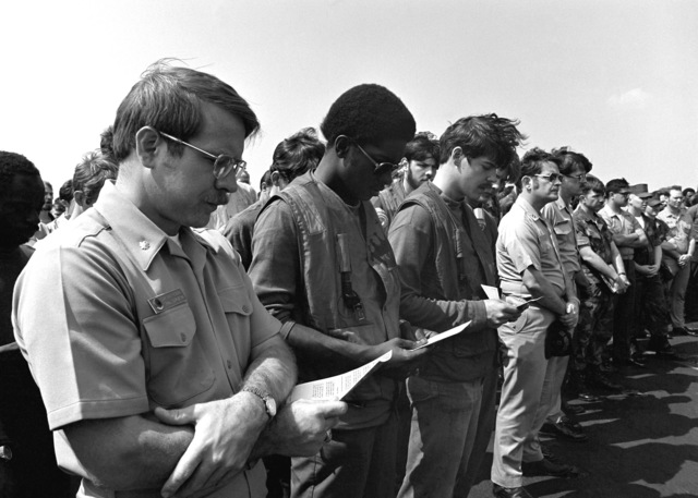 Crewmen participate in a memorial service on the flight deck of the aircraft carrier USS INDEPENDENCE (CV-62). The service is being held for one of their fellow crewmen