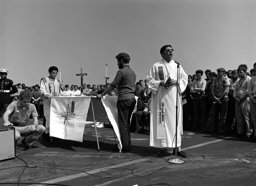 LT. CMDR. George E. Dobes, Chaplain Corps, conducts a memorial service on the flight deck of the aircraft carrier USS INDEPENDENCE (CV-62). The service is being held for an INDEPENDENCE crew