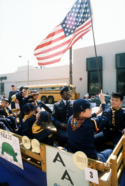 Cub Scout Billy Parnell raises the American flag while members of the Turtle Brigade salute. Looking on is MASTER Sgt. Gary Kelly, a member of the Non-Commissioned Officers Academy Graduates Association (NCOAGA), one of the base personnel who helped handicapped scouts participate in the annual National Orange Show Parade